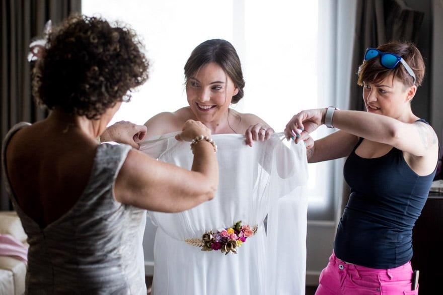 Novia poniéndose un vestido de novia de la firma Jesús Peiró de Novias Sol de O Carballiño en su boda en la Bodegas Cepa 21