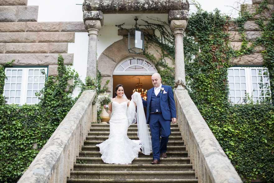 Novia y padrino bajando las escaleras del Pazo do Tambredurante una boda en el Salón de Los Olivos