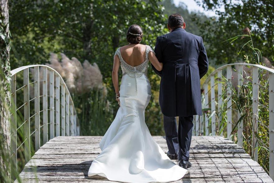 Espalda del vestido de la novia de Rosa Clará en el puente del Pazo do Tambre el día de su boda