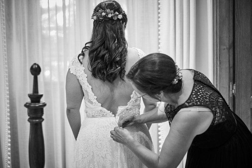 Habitación del Pazo Montesclaros, madre ayudando a poner a la novia el vestido de Pronovias